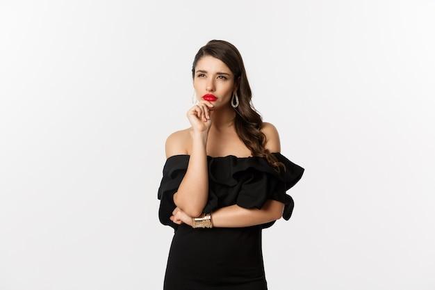 Мода и красота. изображение вдумчивой гламурной женщины, глядя в сторону, прищурившись, думая, стоя в черном платье на белом фоне.