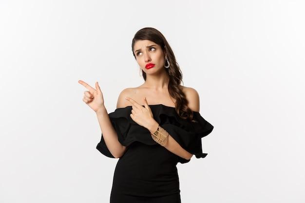ファッションと美容。黒いドレスを着た嫉妬深いグラマーな女性が指を左に向けて見ていると、失望した白い背景をやめます。