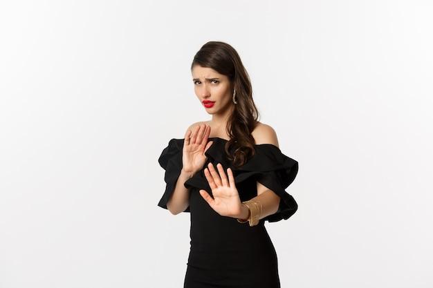 ファッションと美容。白い背景の上に黒いドレスを着て立って、立ち止まるジェスチャーを示し、怖がって見える、遠ざかることを求めている気が進まない心配している女性。