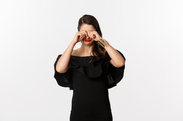 Мода и красота. грустная и мрачная женщина в черном платье плачет, протирает глаза и дуется, стоя на белом фоне