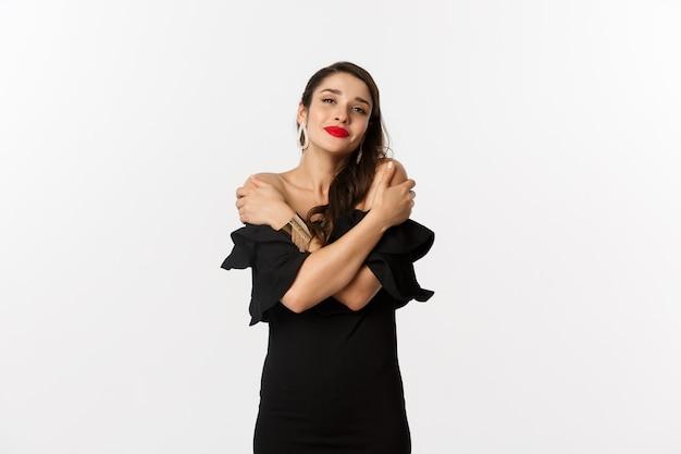ファッションと美容。黒のドレスを着て、自分の体を抱きしめ、抱きしめ、笑顔で、白い背景の上に立っている官能的で優しい女性