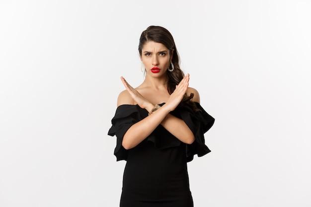 ファッションと美容。黒のドレスを着た真面目で自信に満ちた女性モデル、クロスサインと眉をひそめている、ジェスチャーを停止、ノーと言って、白い背景の上に立っています。