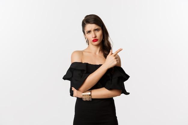 ファッションと美容。赤い唇、黒いドレス、白い背景の上に立って、何か足の不自由で退屈なものに人差し指を向けている懐疑的な魅力の女性。
