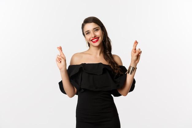 ファッションと美容。黒のドレス、赤い唇、楽観的に見え、指を交差させながら笑顔、願い事をし、白い背景の上に立っているスタイリッシュな魅力的な女性。
