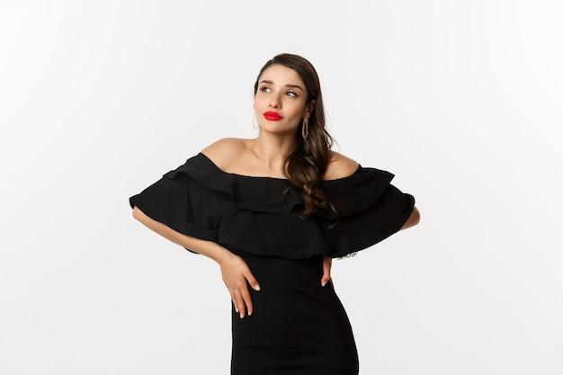 ファッションと美容。黒のドレス、化粧、赤い唇のスタイリッシュな現代女性、白い背景の上に自信を持ってポーズをとって、白い背景の上に立っています。