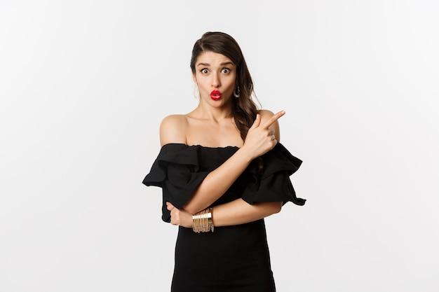 Мода и красота. удивленная женщина в черном платье указывая пальцем в верхнем правом углу, показывая рекламу, стоя на белом фоне.