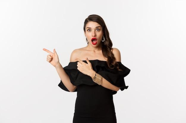 패션과 뷰티. 왼쪽 손가락을 가리키는 검은 매력적인 드레스에 놀란 여자는 광고를 표시하고 놀랍게도 흰색 배경을 쳐다보고 있습니다.