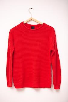패션과 옷 개념. 흰 벽에 옷걸이에 여자 빨간 니트 따뜻한 스웨터