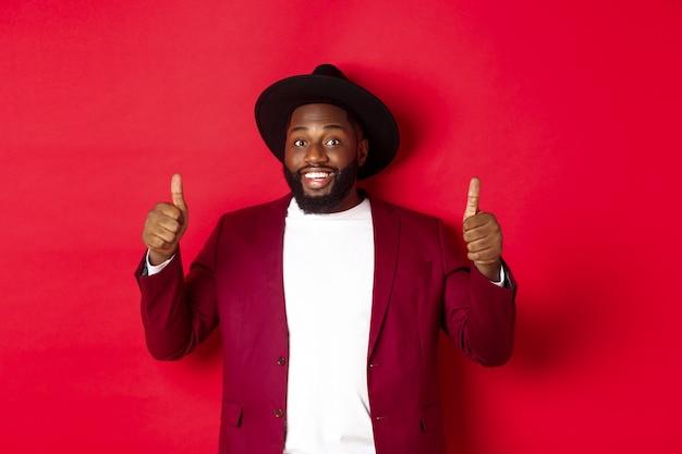 패션 및 파티 개념입니다. 고급 재킷을 입은 쾌활한 아프리카계 미국인 남자, 새해 크리스마스를 축하하고, 엄지손가락을 치켜들고 웃고, 좋아하고, 빨간색 배경을 승인합니다.