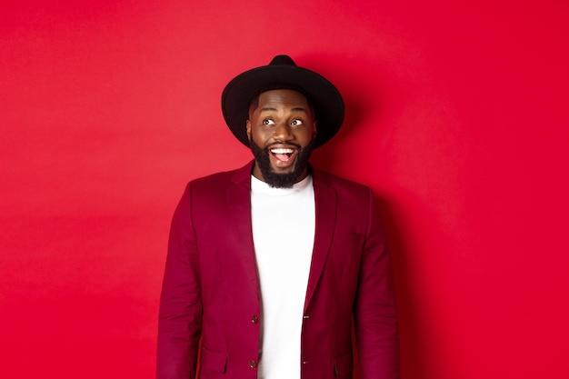 ファッションとパーティーのコンセプト。ロゴを見て、幸せな笑顔で左上隅を見つめ、赤い背景に立って興奮したアフリカ系アメリカ人の男。
