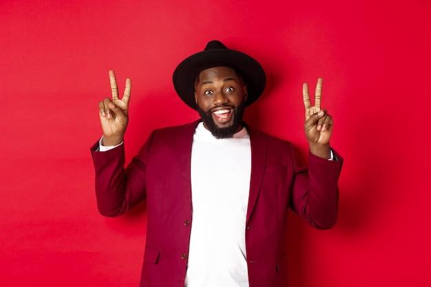 ファッションとパーティーのコンセプト。楽しんで、平和の兆候を示し、笑顔で、赤い背景に帽子をかぶって立っているハンサムな黒人男性。