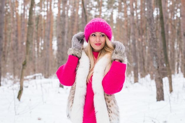 ファッションと人々のコンセプト-冬の雪のピンクの暖かいジャケットに立っている魅力的な若い女性