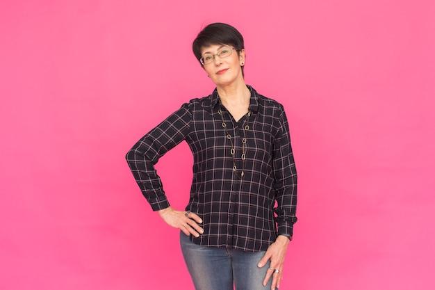 Концепция моды и людей - красивая женщина средних лет в очках, одетых в рубашку и джинсы на розовом фоне.