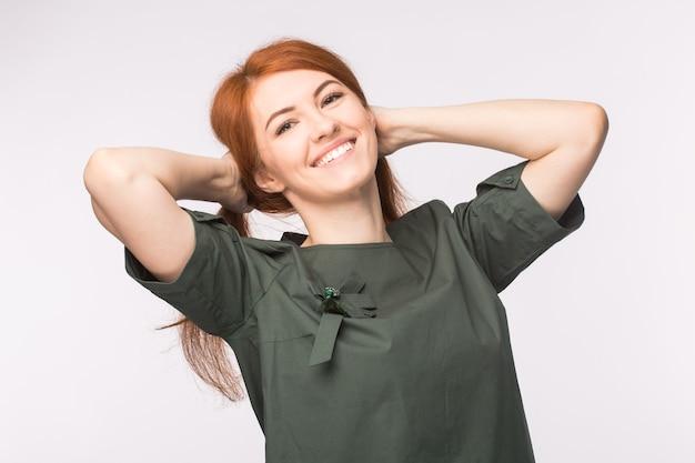 ファッションと人々の概念-白い背景の上に笑顔の赤い髪の美しい若い女性