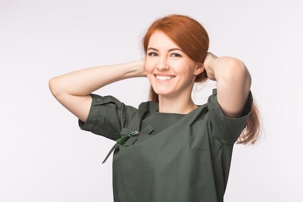 ファッションと人々のコンセプト-白い壁に笑みを浮かべて赤い髪の美しい若い女性。