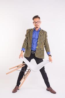 ファッションと人々の概念-白い背景の上の椅子とねじれメガネのハンサムな男。