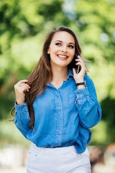 Мода и сексуальная женщина гуляет и разговаривает по мобильному телефону на городской улице