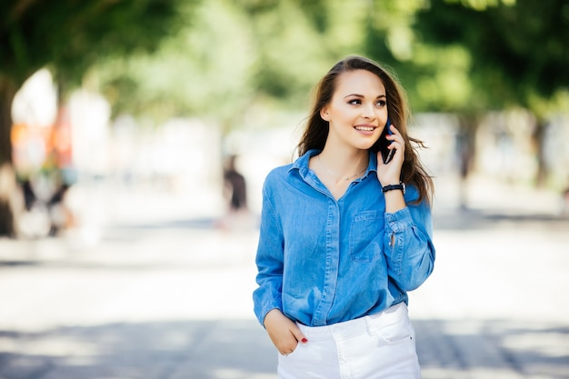 街の通りを歩いて携帯電話で話しているファッションとセクシーな女性