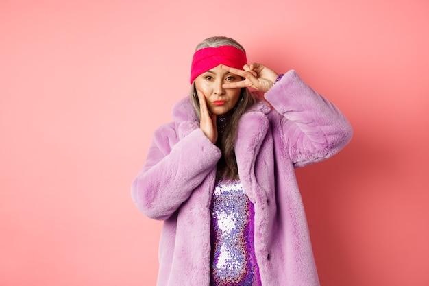 ファッションとショッピング。スタイリッシュなフェイクファーのコートとヘッドバンドで美しいアジアの年配の女性、顔に平和のサインを作り、カメラ、ピンクの背景で生意気で自信を持って見えます。