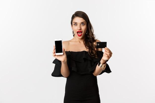 ファッションとショッピングのコンセプト。スマートフォンの画面とクレジットカードを表示し、興奮しているように見え、オンラインで購入、白い背景に驚いた美しい女性。