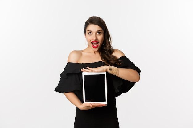 ファッションとショッピングのコンセプト。タブレット画面でオンラインウェブサイトのプロモーションオファーを表示し、興奮したカメラを見て、黒いドレス、白い背景で立っている驚いた若い女性。