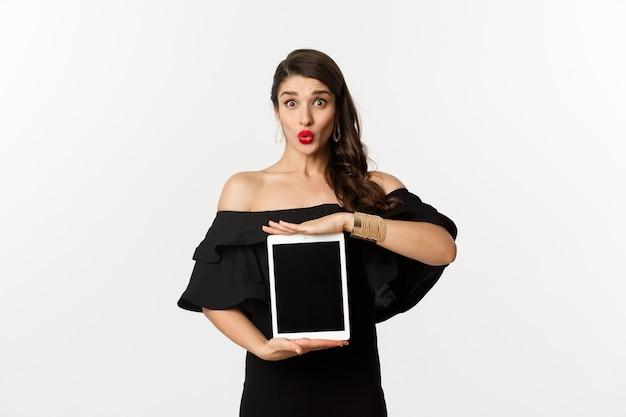 패션과 쇼핑 개념. 빨간 립스틱, 검은 드레스, 태블릿 화면을 표시 하 고 흥분 찾고, 흰색 배경 위에 서있는 아름 다운 여자.