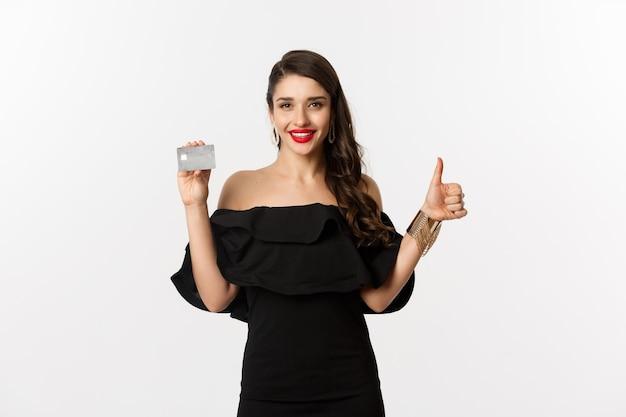패션 및 쇼핑 개념입니다. 신용 카드를 보여주는 검은 드레스에 만족한 세련된 여성, 승인, 추천, 흰색 배경 위에 서 있는 엄지손가락을 만듭니다.