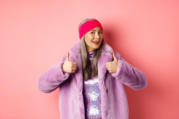 ファッションとショッピングのコンセプト。はいと言っているスタイリッシュなアジアのおばあちゃん。冬のフェイクファーのコートを着たトレンディな韓国のシニア女性は、承認を得て親指を立て、良い製品、ピンクの背景を賞賛しています。