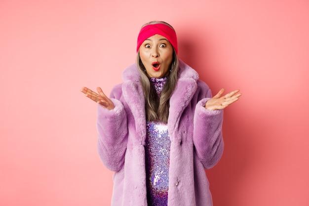 ファッションとショッピングのコンセプト。スタイリッシュなフェイクファーのコートとヘッドバンドで驚いた年配のアジア人女性がカメラに驚いて、良いニュース、ピンクの背景を喜んでいます。