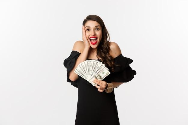 ファッションとショッピングのコンセプト。お金の賞金を喜んで、ドルを保持し、興奮から叫んで、白い背景の上に黒いドレスを着て立っている女性。