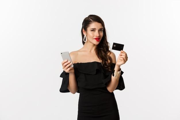 Концепция моды и покупок. женщина с красными губами, черное платье, думая, что купить, держа кредитную карту и мобильный телефон, стоя на белом фоне.