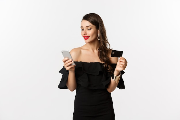 Концепция моды и покупок. молодая привлекательная женщина делает покупки в интернете, покупая в интернете с помощью кредитной карты и смартфона, на белом фоне.