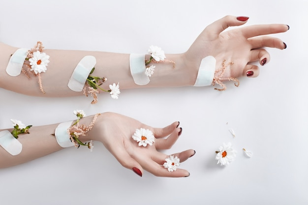 Fashion art hand care and chamomile flowers