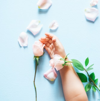 Fashion art  hand of a little child holding flowers on blue background