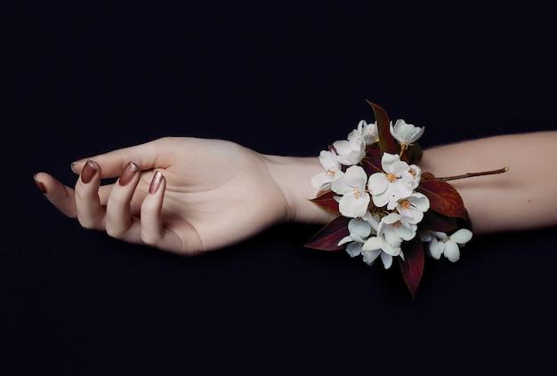 夏のファッション アートの手の女性と、明るい対照的な化粧をした手に花を咲かせます。創造的な美しさの写真は、色付きの影と対照的な背景にテーブルに座っている女の子を手します。スキンケア