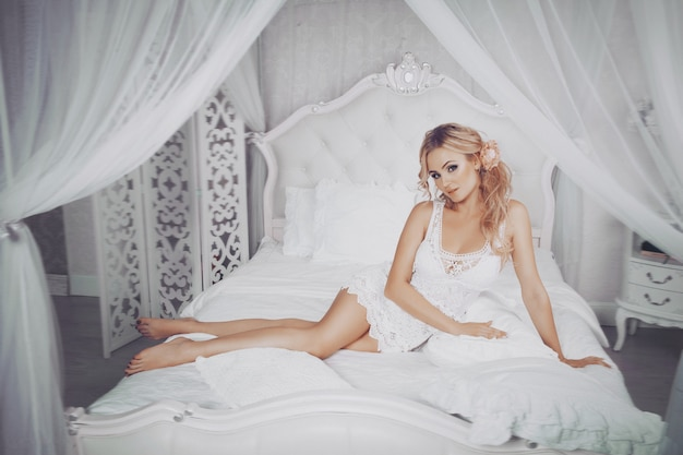 Fashion art photo of beautiful sensual young blonde woman in white lingerie negligee with make up and hairstyle in her boudoir. home bedroom white interior. lady getting ready for bed