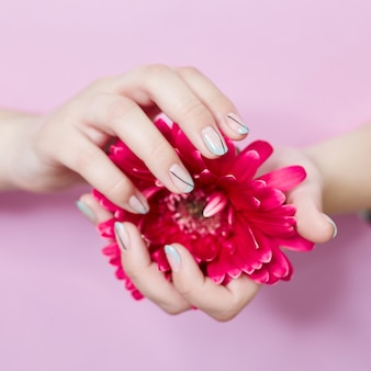 Fashion art portrait woman flowers in her hand with a bright contrasting makeup nail. creative beauty photo girl a contrasting pink wall with colored shadows