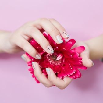 밝은 대조 메이크업 손톱으로 그녀의 손에 패션 아트 초상화 여자 꽃. 창조적 인 아름다움 사진 소녀 색깔의 그림자와 대조 분홍색 벽