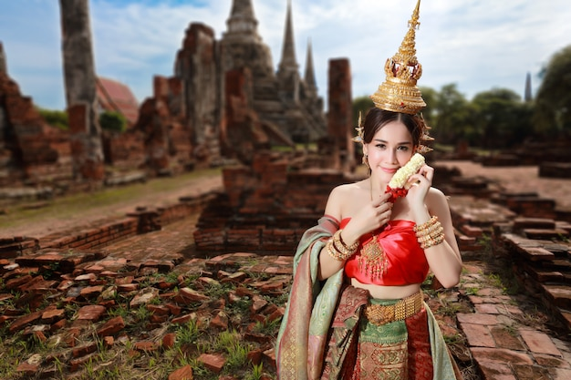 Fashion asian girl in thai traditional costume in ancient temple with steering wheel flower in hand