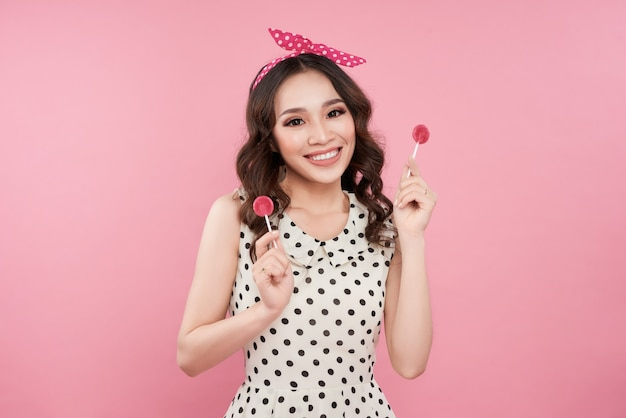 Fashion asian woman holding lollipop, posing against pink background