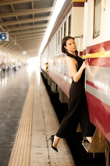 Fashion asian woman wear black luxury dress. lgbt transgender model travels on train at station railway. concept after post covid