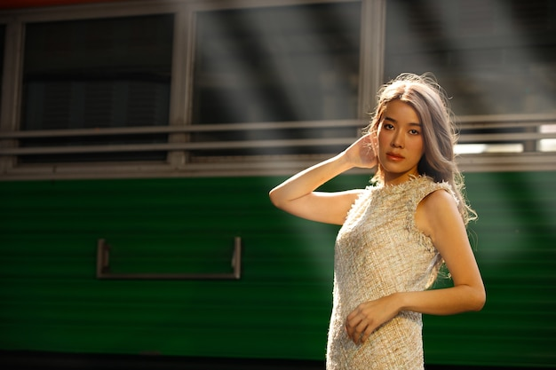 Fashion asian woman wear cream luxury coat dress dying hair color. young model travels on train at station railway in summer.