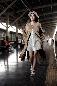Fashion asian woman wear cream luxury coat dress with hat. young model travels on train at station railway in summer. concept after post covid