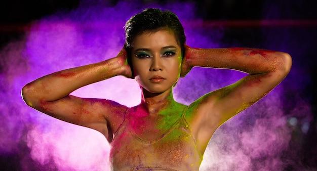 Азиатская женщина моды с разноцветной пылью и разноцветным дымом в воздухе