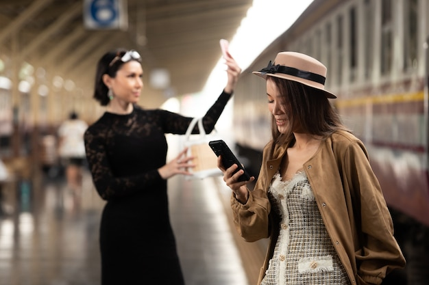 Fashion asian women wear cream luxury coat dress. lgbt transgender and young woman lesbian lover travels on train station and using map in smart phone.