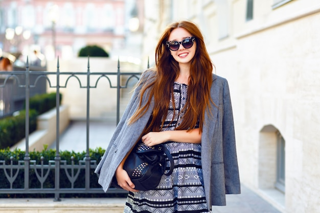 Fashion autumn portrait of stylish ginger woman, posing on the street, feminine tender smart casual outfit, vintage sunglasses, long hairs, street style.