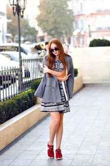 Moda ritratto autunnale di elegante donna allo zenzero, in posa per strada, abbigliamento casual elegante tenero femminile, occhiali da sole vintage, capelli lunghi, street style.