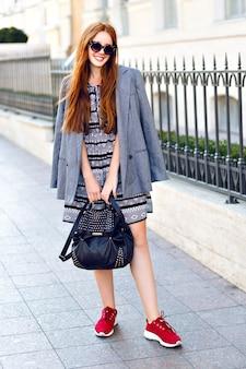 Fashion autumn portrait of stylish ginger woman, posing on the street