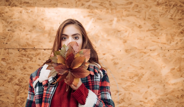 Fashion autumn portrait woman with yellow maple leaves on yellow wooden background