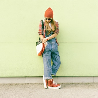 Fashion autumn style student girl at the wall in a stylish clothes
